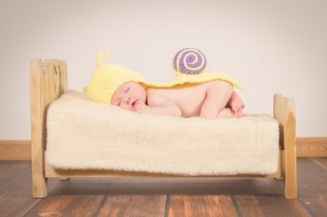 miminko ve šnečím oblečku na dřevěné postýlce